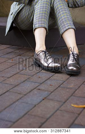 Close Up Woman Legs Weared Shortened Pants And Glossy Stylish Boots With Shoelaces On The Background