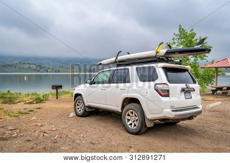 Fort Collins, CO, USA - July 22, 2019: Toyota 4Runner SUV with a performace stand up paddleboard on roof racks at a picnic and swimming area on shore of Horsetooh Reservoir on a foggy summer morning.