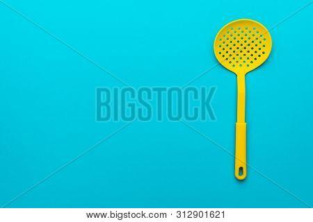 Top View Photo Of Vivid Plastic Kitchen Skimmer Spatula. Minimalistic Flat Lay Image Of Skimmer Spat