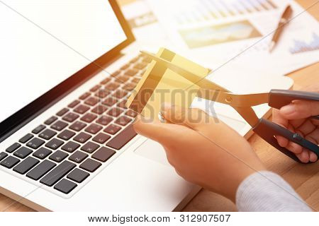 Woman Use Scissors To Cut Credit Cards In Hand In Front Of Computer Laptop