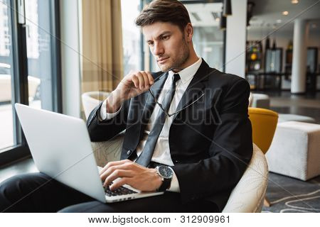 Portrait of serious young businessman wearing formal black suit sitting on armchair with laptop computer in hotel hall