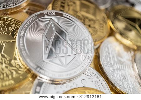 Eos Cryptocurrency Coin With Big Eos Symbol In The Centre Of It. Eos Physical Coin On The Stack Of O