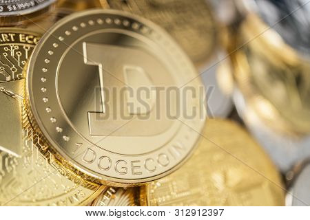 Dogecoin Physical Coin On The Stack Of Other Different Cryptocurrencies. Close-up Photo Of Dogecoin