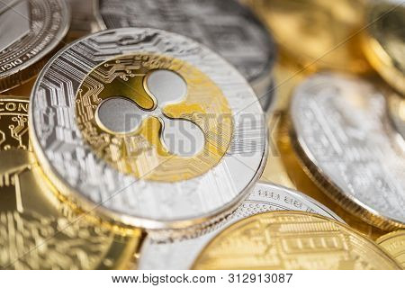 Ripple Physical Coin On The Stack Of Other Different Cryptocurrencies. Close-up Photo Of Ripple With
