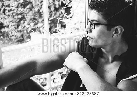 Handsome Latino Man With Eye Glasses Sitting In Window