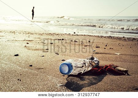 Plastic Bottle And Trash Lying On The Shore Of The Beach And Polluting The Sea And The Marine Life,