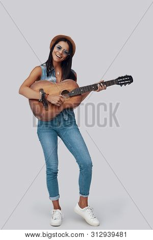 Full Length Of Attractive Stylish Young Woman Playing Acoustic Guitar And Smiling While Standing Aga