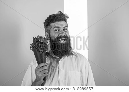 Flowers Delivery Concept. Man With Beard Cheerful Face Holds Bouquet Fresh Flowers. Hipster With Bea