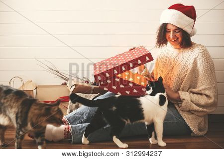 Stylish Happy Girl In Santa Hat And Her Cats Opening Christmas Gift Box With Magic Light In Decorate