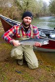 A steelhead fisherman holds his trophy fish by his boat and the river in Oregon. poster