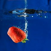 A fresh strawberry dropping in water splash bubble poster