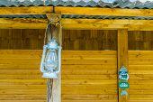 Vintage miner lantern hanging at a beach hut, nostalgic lighting poster