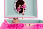 small green frog sitting in a pink and teal jewelry box over white poster