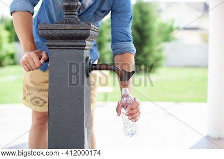 A Man Hand Pours Water From A Tap From A Drinking Column Into A Plastic Bottle. Сity Water Tap With