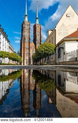 Wroclaw, Poland - May 3 2020: Facade Of Cathedral Of St. John The Baptist Reflected In Puddle