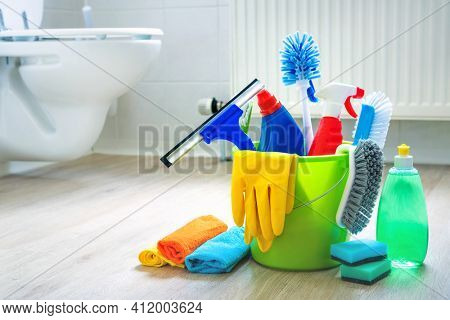 Various cleaning items and supplies in a bucket on the bathroom floor