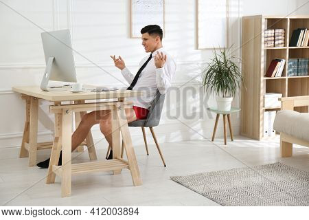 Businessman In Shirt And Underwear Having Video Call On Computer At Home Office