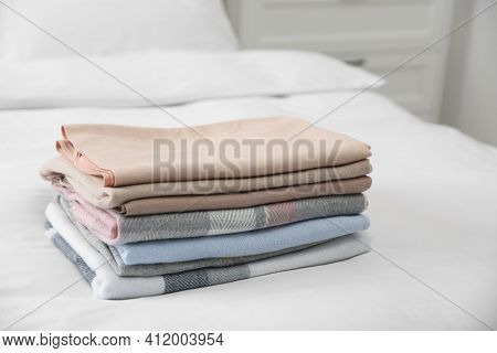 Stack Of Folded Cashmere Clothes On Bed