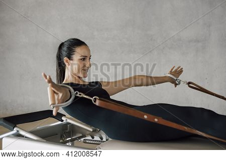 Brunette Fit Woman, Strong Female Instructor, In Black Sport Clothing, Doing Pilates Routine In A Re
