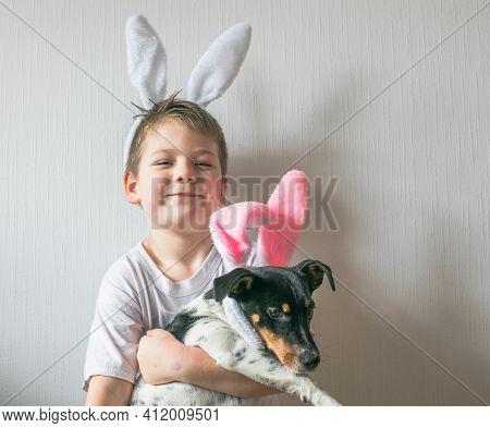 Little Cute Boy  Wearing Easter Bunny Ears, Smile  And Holding Dog With Easter Bunny Ears. Easter Ki