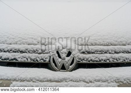 Close-up Of A Chrome Volkswagen Logo On A Front Grid Covered With The Snow. Moscow, Russia - March 1