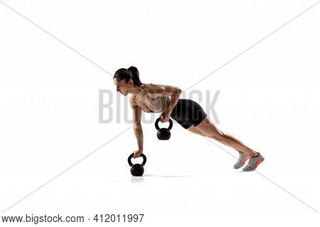 Balance. Caucasian Professional Female Athlete Training Isolated On White Studio Background. Muscula