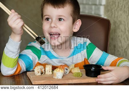 Little Boy Enjoys Eating Sushi Rolls. Happy Boy Ready For Eating Sushi.