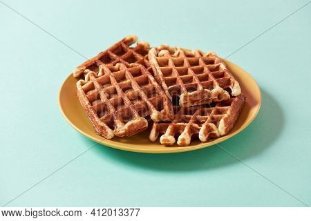 Homemade Waffles. Freshly Baked Belgian Waffles With Sugar On Yellow Plate Isolated Over Blue Backgr