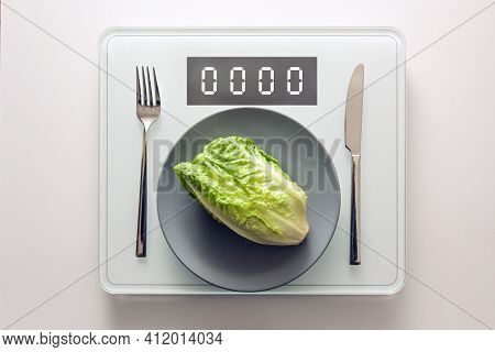 Fresh Green Lettuce Or Baby Cos On A Gray Plate And Cutlery On A Digital Weight Scale Showing Zero,
