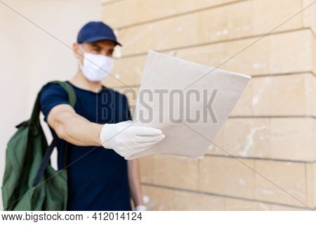 Postman In Uniform In Latex Gloves And Medical Mask Safity Delivering Letters To Mailbox Of A Recipi
