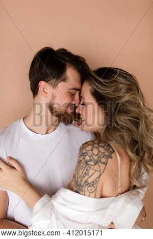 Portrait Of A Man And Woman In An Embrace On Beige Background. Couple Smiling. Romantic Love. Couple