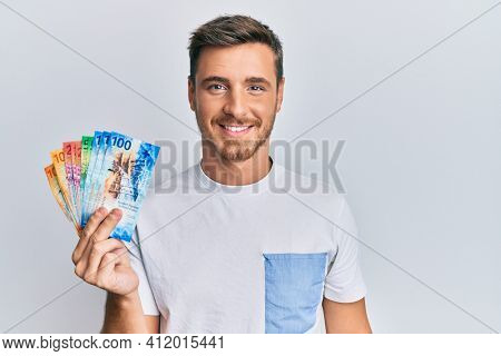 Handsome caucasian man holding swiss franc banknotes looking positive and happy standing and smiling with a confident smile showing teeth