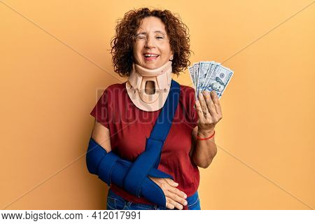 Beautiful middle age mature woman wearing cervical collar and sling holding insurance dollars winking looking at the camera with sexy expression, cheerful and happy face.