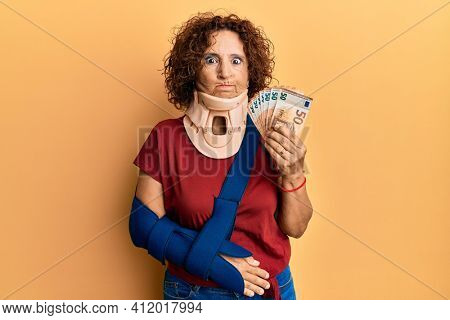 Beautiful middle age mature woman wearing cervical collar and sling holding insurance euros skeptic and nervous, frowning upset because of problem. negative person.