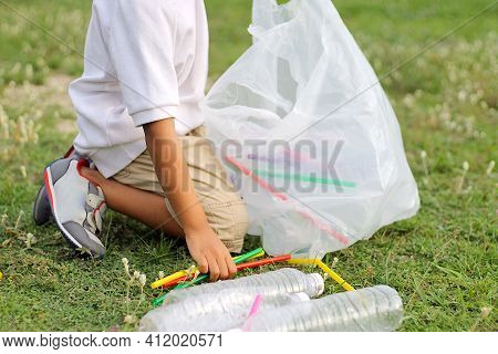 At The City Public Park. Asian Child Boy Is A Volunteer For Clean Up The Field Floor. He Picking Up