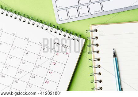 April 2021 Calendar With Note Book On Green Color Background.