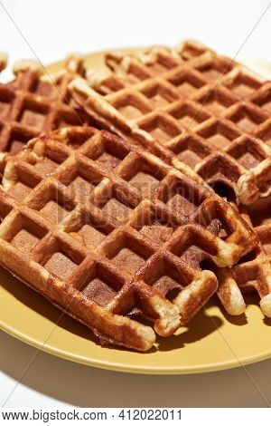 The Best Waffle Recipe. Close Up Of Freshly Baked Belgian Waffles With Sugar On Yellow Plate Isolate