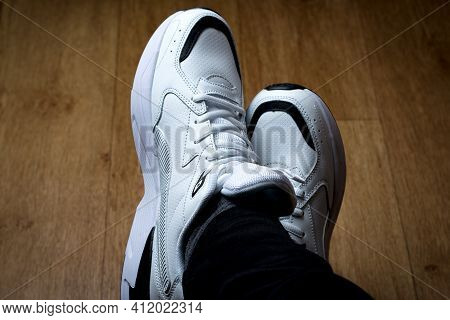 White Sneakers. White Sneakers With Black Stripes On Male Feet.