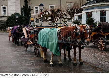 Horses With Wagons Called Fiaker Waiting For Tourists In The Old Part Of Town In Winter On The Main