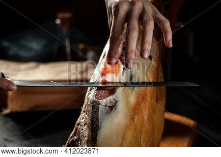 Dry Spanish Ham, Iberian Ham Cutter On Black Background. Iberian Ham Cutter. Traditional Spanish Ham