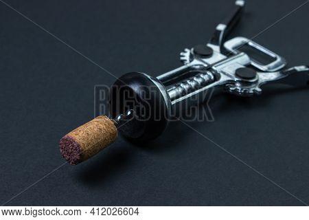 Corkscrew On A Dark Background. Wine Cork On A Corkscrew On A Black Background. Steel Corkscrew