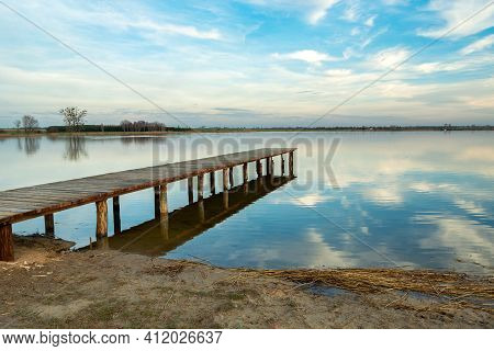 Long Wooden Jetty Towards A Calm Lake, Reflection Of The Clouds In The Water, Staw, Poland