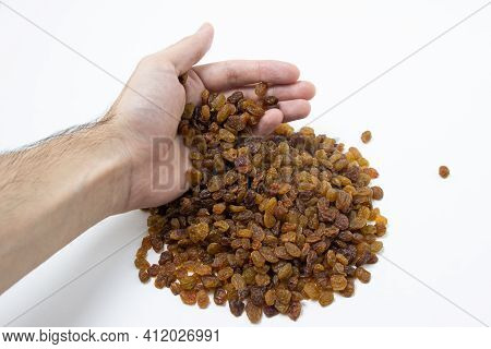 Isolated Raisins On A White Background. Raisins In A Man\'s Hand. Healthy Dried Fruit. Dried Grapes.