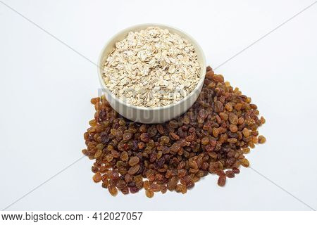 Oatmeal And Raisins On A White Background. Healthy Diet. A Full Cup Of Oatmeal, Raisins Scattered Ne