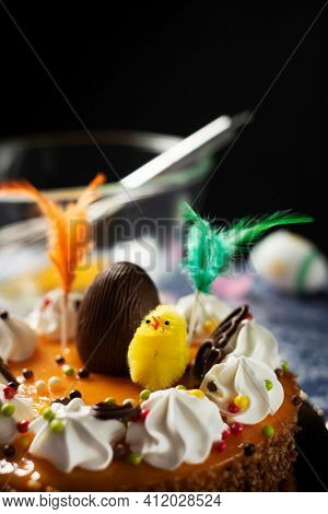 closeup of a spanish mona de pascua, a cake eaten on Easter Monday, ornamented with a plush chick, a chocolate egg and feathers of different colors, on a table