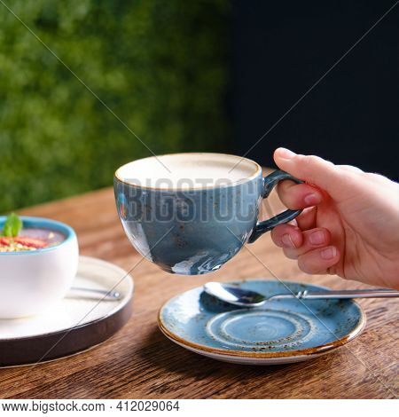 Woman Holding A Cup Of Coffee In A Cafe, Hand Close-up. Berry Dessert And Milk Drink On A Table In A