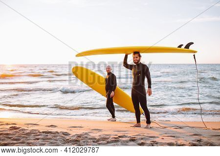 Two Young Surfers In Black Wetsuit With Yellow Surfing Longboards At Ocean Coast At Sunset. Water Sp