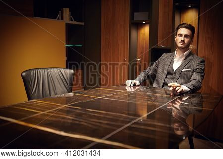 Handsome brunet man in an elegant suit relaxing in a luxury apartment with a cigar. Mafia. Male beauty, fashion.