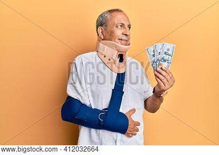 Handsome mature injured man wearing cervical collar and sling holding insurance money smiling looking to the side and staring away thinking.