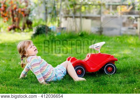 Little Active Adorable Toddler Girl Falling Down From Toy Car, Having Pain And Crying, Outdoors. Ups